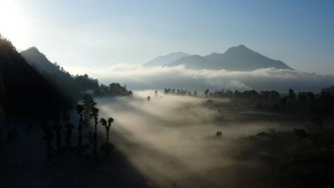 Drone-Shot-Passing-Over-Low-Hanging-Fog-Surrounding-Mount-Batur