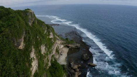 Drohnenschuss-Fliegt-über-Eine-Klippe-An-Der-Küste-Von-Uluwatu
