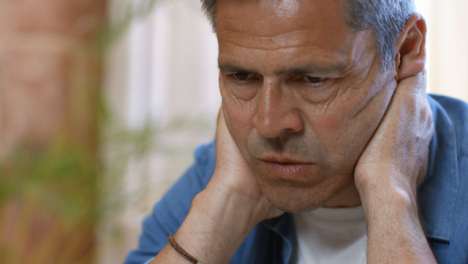 Close-Up-Shot-of-Middle-Aged-Man-Looking-Visibly-Concerned