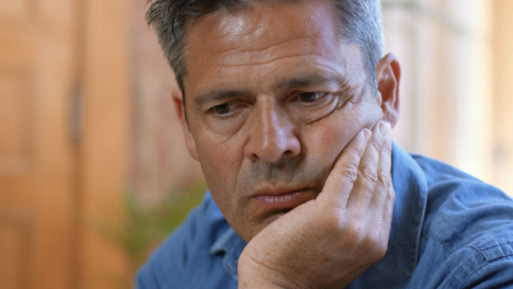 Close-Up-Shot-of-Middle-Aged-Man-Looking-Visibly-Stressed-and-Concerned