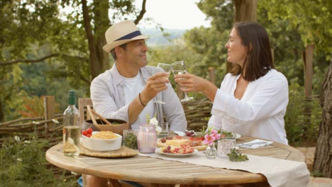 Wide-Shot-of-Middle-Aged-Couple-Bringing-Their-Wine-Glasses-Together
