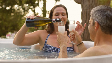 Over-the-Shoulder-Shot-of-Middle-Aged-Couple-Pouring-Champagne-in-Hot-Tub