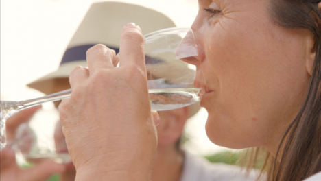 Pull-Focus-Shot-from-Middle-Aged-Man-to-His-Wife-as-They-Drink-Wine