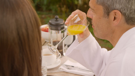 High-Angle-Shot-of-Middle-Aged-Man-Talking-to-Wife-During-Outdoor-Breakfast