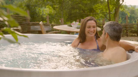 Wide-Shot-of-Middle-Aged-Couple-Talking-In-Hot-Tub