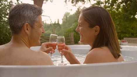 Close-Up-Shot-of-Middle-Aged-Couple-Drinking-Champagne-In-Hot-Tub-