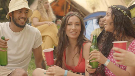 Tracking-Shot-Around-Group-of-Young-Festival-Goers-as-One-Brings-Drinks-Over