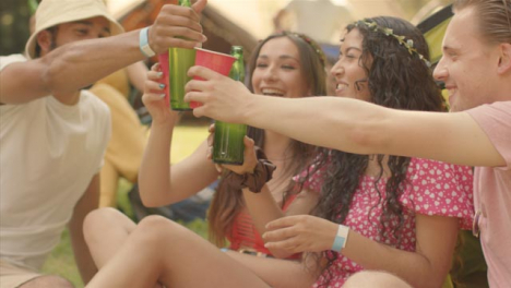 Tracking-Shot-Around-Group-of-Some-Young-Festival-Goers-as-One-Brings-Drinks-Over
