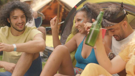 Tracking-Shot-of-Young-Festival-Goers-Sitting-with-One-Another-Talking-and-Drinking