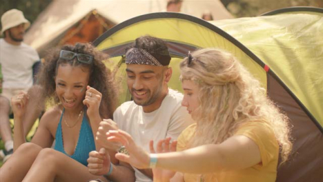 Medium-Shot-of-Young-Festival-Goers-Joking-and-Dancing-by-Their-Tent