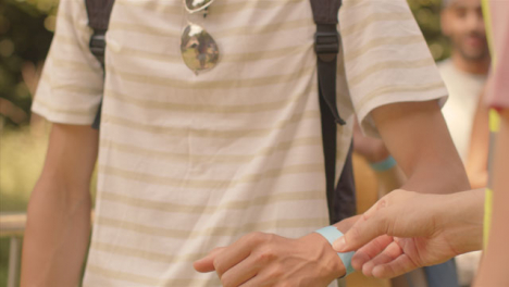 Close-Up-Shot-of-Festival-Goers-Showing-Wrist-Bands-to-Security-Guard