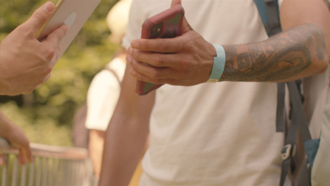 Close-Up-Shot-of-Festival-Goers-Showing-Electronic-Tickets-to-Security-Guard