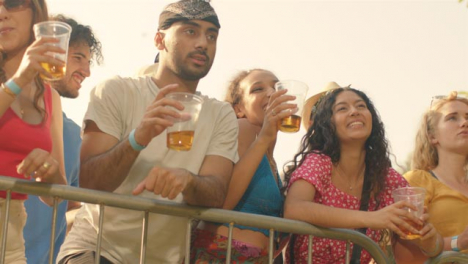Low-Angle-Shot-of-a-Group-of-Festival-Goers-at-Stage-Barrier-Enjoying-Music