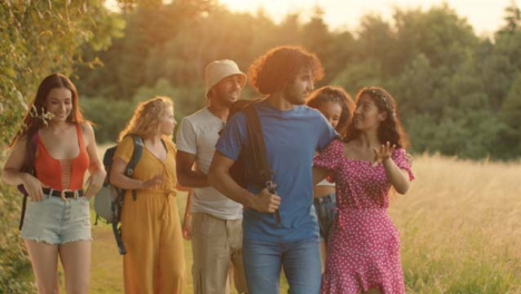 Tracking-Shot-of-a-Multi-Ethnic-Group-of-Friends-Walking-at-Sunset