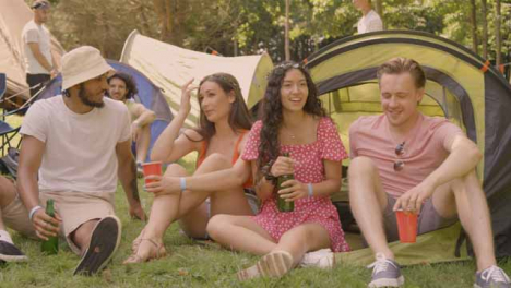 Wide-Shot-of-Young-Festival-Goers-Sitting-Down-Drinking-and-Talking