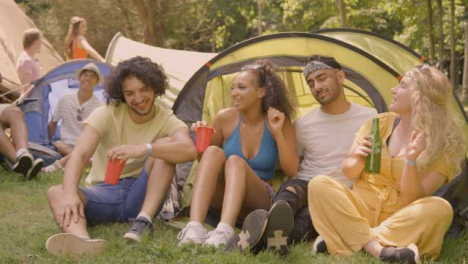 Sliding-Shot-of-Festival-Goers-Drinking-and-Messing-Around-by-Their-Tent