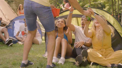 Sliding-Shot-of-Young-Festival-Goer-Bringing-His-Friends-Some-Alcoholic-Drinks