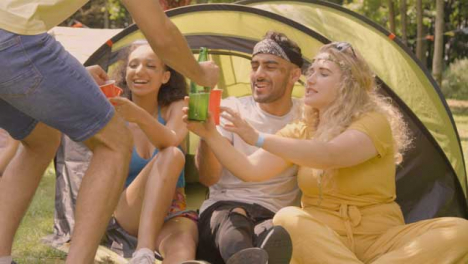 Sliding-Shot-of-Some-Festival-Goers-Drinking-and-Messing-Around-by-Their-Tent