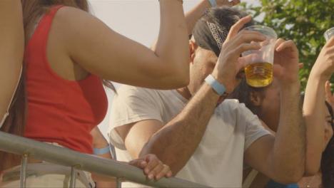 Disparo-De-ángulo-Bajo-De-Jóvenes-Asistentes-Al-Festival-Disfrutando-De-La-Música-En-La-Barrera-Del-Escenario