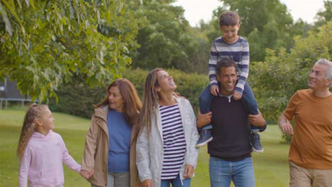Tracking-Shot-of-Family-Walking-Together-Through-Gardens