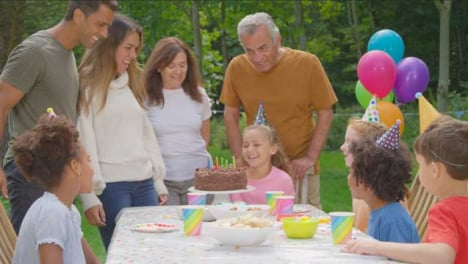 Handheld-Shot-of-Family-Clapping-Child-After-Blowing-Out-Candles-On-Birthday-Cake