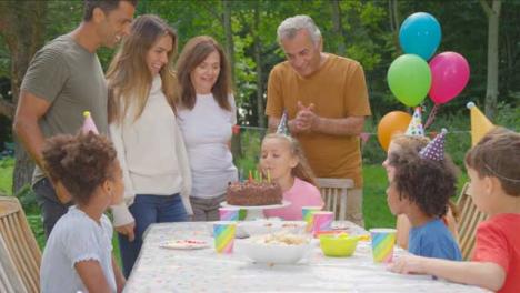 Handheld-Shot-of-Family-Singing-Happy-Birthday-to-Young-Girl