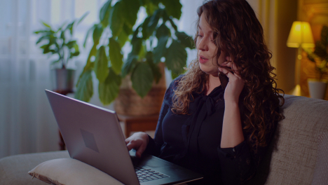 Portrait-Of-Businesswoman-Working-On-Laptop-While-Talking-On-Mobile-Phone