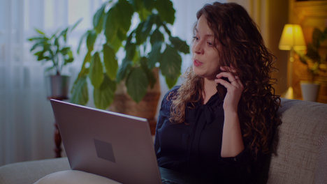 Portrait-Of-Businesswoman-Working-On-Laptop-While-Talking-On-Mobile-Phone-1