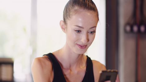 Beautiful-Female-Athlete-Using-Mobile-Phone-During-Break-After-Workout-At-Fitness-Club