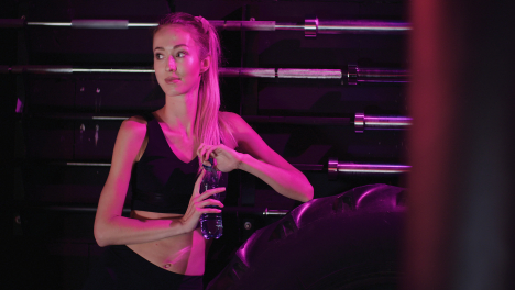 Smiling-Confident-Slim-Female-Athlete-Drinking-Water-From-Bottle-At-Fitness-Club