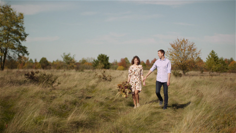 Loving-Couple-Walking-On-A-Meadow-In-Summer-While-Holding-Hands