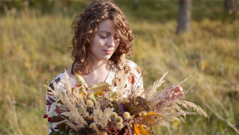 Medium-Shot-Of-Woman-Looking-At-Bouquet-Of-Wild-Flowers-In-Summer