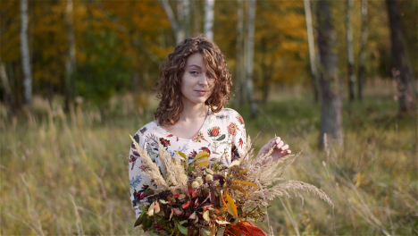 Medium-Shot-Of-Woman-Looking-At-Bouquet-Of-Wild-Flowers-In-Summer-1