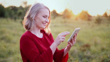 Attractive-Smiling-Woman-Using-Digital-Tablet-Outdoors-In-Summer-8