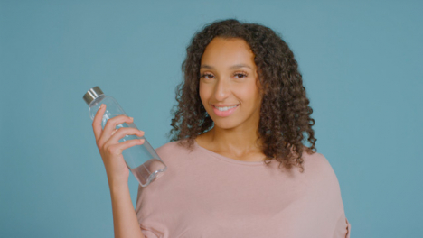 Portrait-Shot-of-Young-Adult-Woman-Smiling-with-Water-Bottle