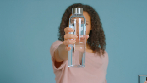 Portrait-Shot-of-Young-Adult-Woman-Drinking-Showing-Water-Bottle-to-Camera-01