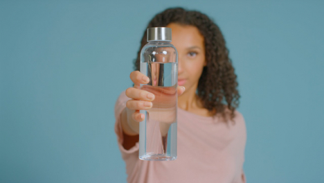 Portrait-Shot-of-Young-Adult-Woman-Drinking-Showing-Water-Bottle-to-Camera-02
