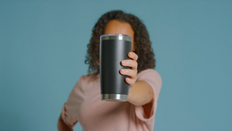 Portrait-Shot-of-Young-Adult-Woman-Holding-Up-Flask-to-Camera