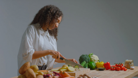 Wide-Shot-of-Young-Adult-Woman-Slicing-Courgette