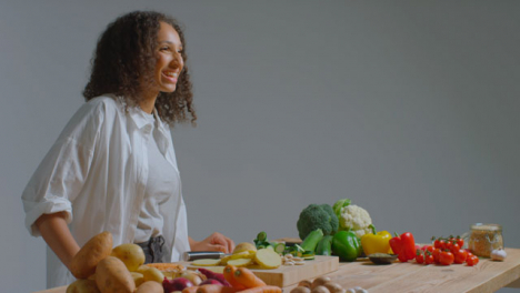 Wide-Shot-of-Young-Adult-Woman-Slicing-Courgette-Before-Laughing-Off-Camera