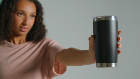 Close-Up-Shot-of-Young-Adult-Woman-Holding-Out-Flask-