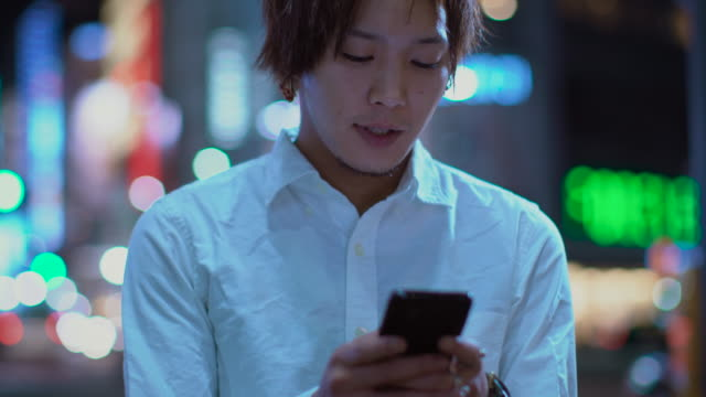 Portrait-of-the-Handsome-Japanese-Alternative-Boy-Using-Mobile-Phone-In-the-Background-Big-City-Advertising-Billboards-Lights-Glow-in-the-Night-