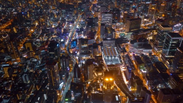Aerial-night-hyper-lapse-over-Osaka-city-Japan-with-Umeda(Osaka)-train-station-and-many-skyscraper-building-and-vehicles-transporting-along-the-road-