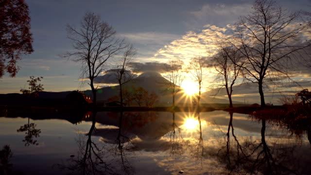 Reflection-of-Mountain-Fuji-with-dry-trees-at-sunrise-near-Fujikawaguchiko-Yamanashi-Japan