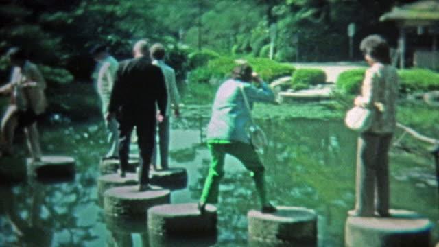 1972:-Personas-a-los-escalones-EN-EL-zen-de-estilo-japonés-y-estanque-