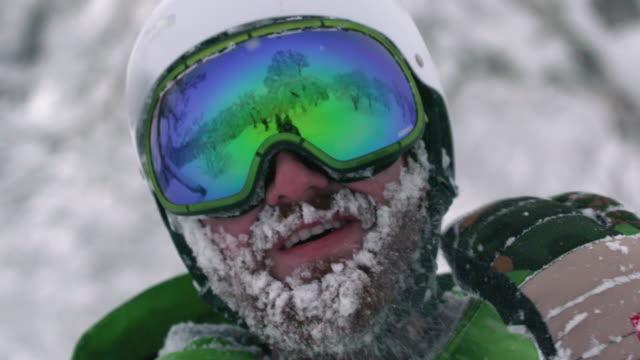 Snowboarder-Skier-Mountainman-Wearing-Helmet-Large-Beard-Full-of-Snow-Shaking-Off-Frozen-Face