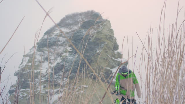 Snowboarder-Hiking-Near-Large-Rocky-Mountains-in-Snowy-Weather