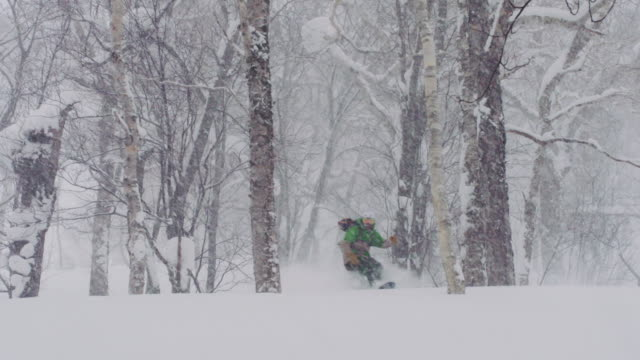 Snowboarding-Deep-Powder-Spraying-Snowy-Flakes-Everywhere-on-a-Snowing-Stormy-Winter-Day
