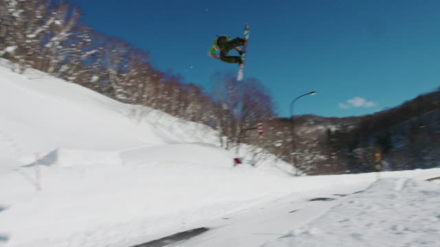 Snowboarder-Jumps-Over-Road-While-Spinning-a-Freestyle-Trick-on-a-Sunny-Winter-Day