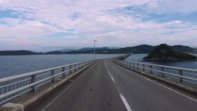 Driving-shot-of-empty-straight-road-over-ocean-Tsunoshima-bridge